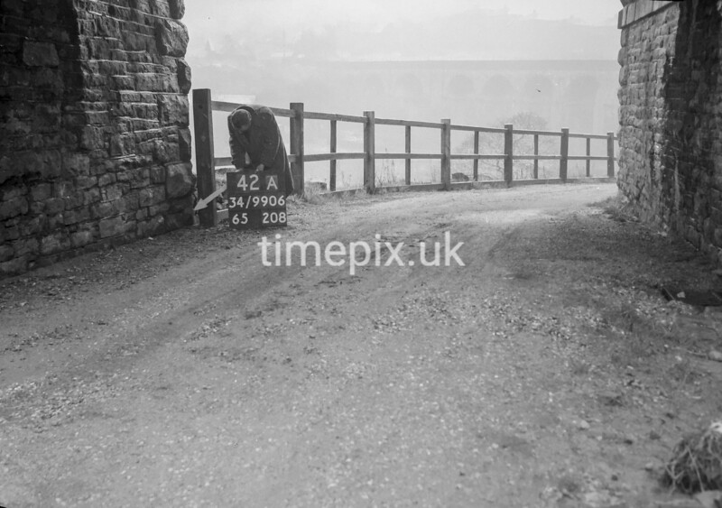 SD990642A, Man marking Ordnance Survey minor control revision point with an arrow in 1950s