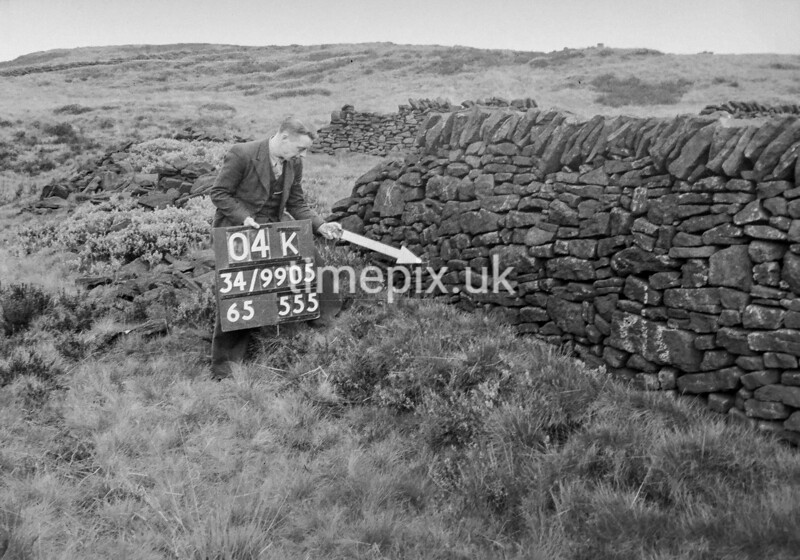 SD990504K1, Man marking Ordnance Survey minor control revision point with an arrow in 1950s