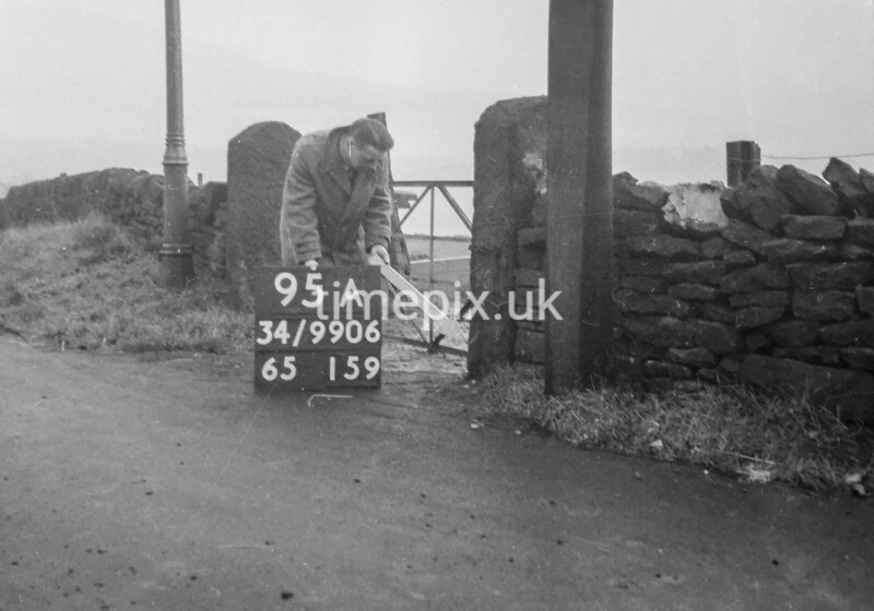 SD990695A, Man marking Ordnance Survey minor control revision point with an arrow in 1950s