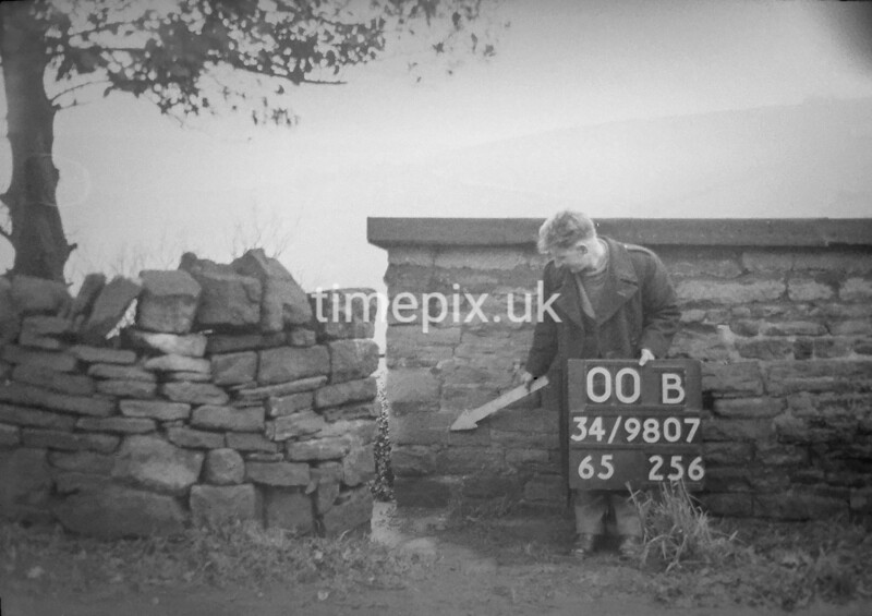 SD980700B, Man marking Ordnance Survey minor control revision point with an arrow in 1950s