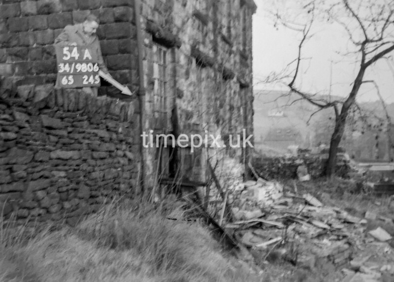 SD980654A, Man marking Ordnance Survey minor control revision point with an arrow in 1950s
