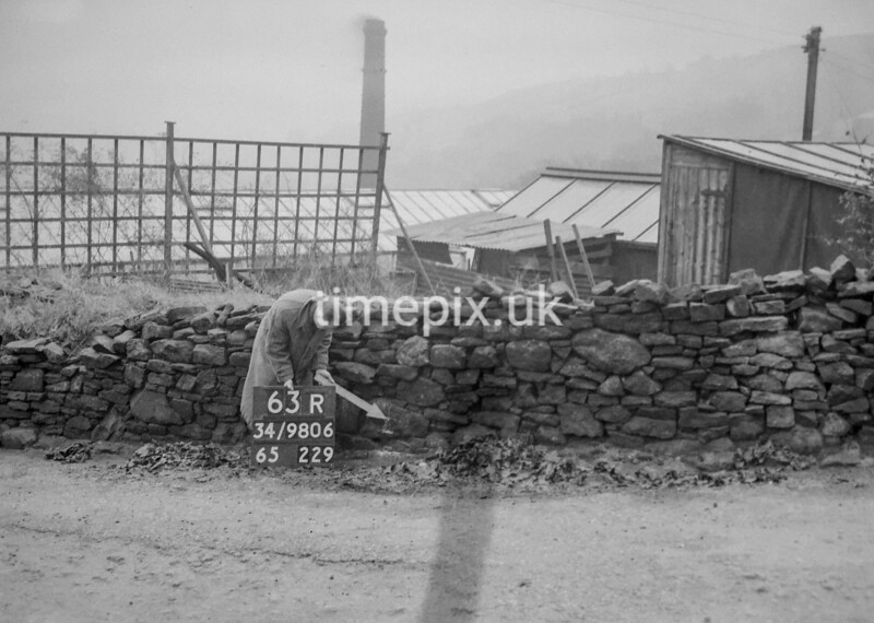 SD980663R, Man marking Ordnance Survey minor control revision point with an arrow in 1950s
