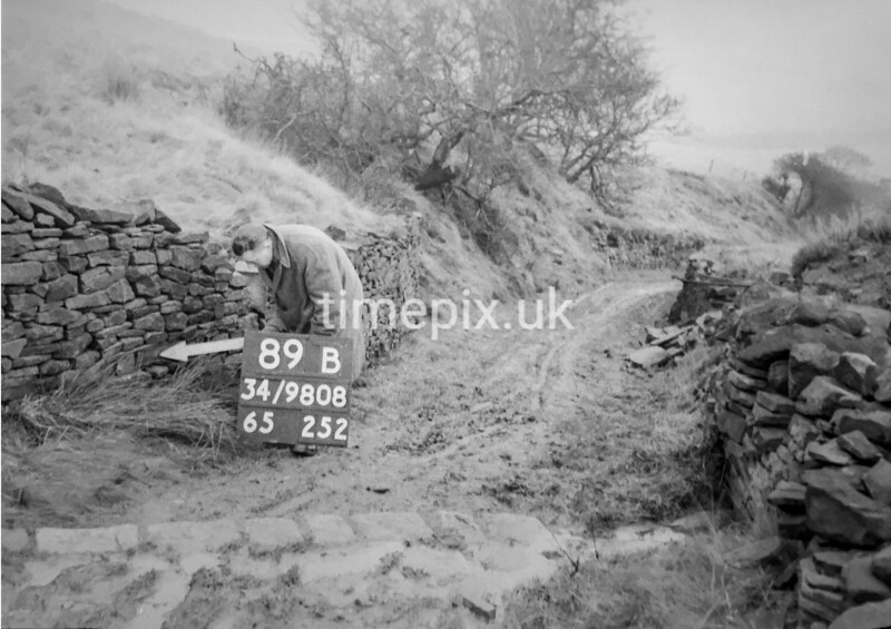 SD980889B, Man marking Ordnance Survey minor control revision point with an arrow in 1950s