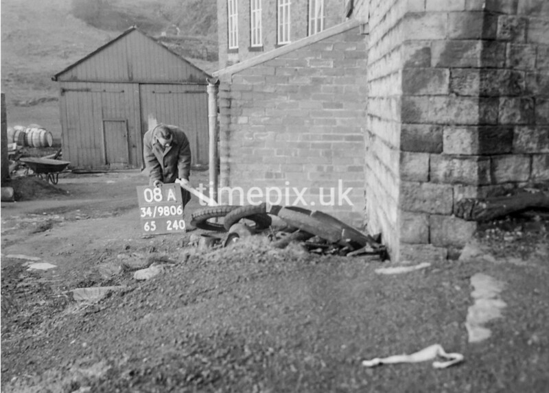 SD980608A, Man marking Ordnance Survey minor control revision point with an arrow in 1950s