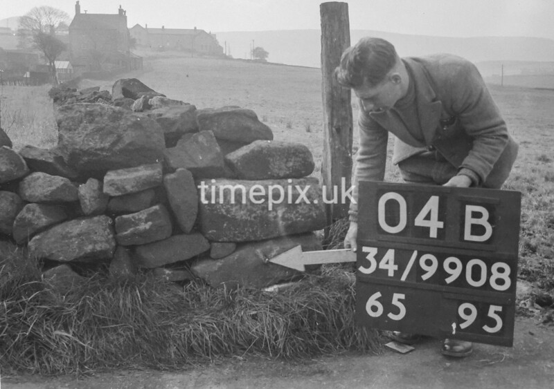 SD990804B, Man marking Ordnance Survey minor control revision point with an arrow in 1950s