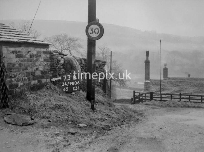 SD980673B, Man marking Ordnance Survey minor control revision point with an arrow in 1950s
