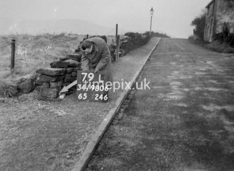 SD980679L, Man marking Ordnance Survey minor control revision point with an arrow in 1950s