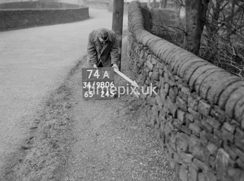 SD980674A, Man marking Ordnance Survey minor control revision point with an arrow in 1950s