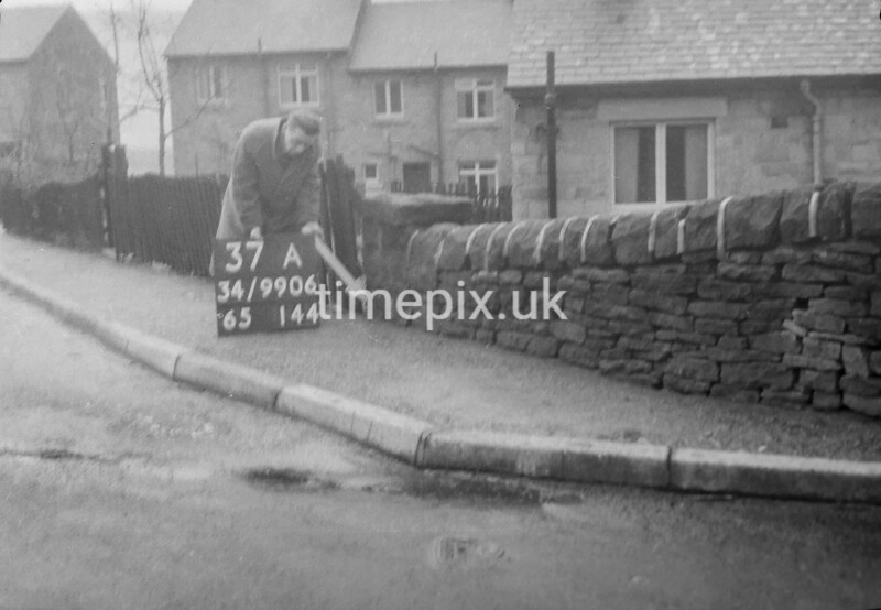 SD990637A, Man marking Ordnance Survey minor control revision point with an arrow in 1950s