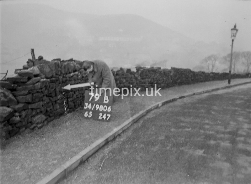 SD980679B, Man marking Ordnance Survey minor control revision point with an arrow in 1950s