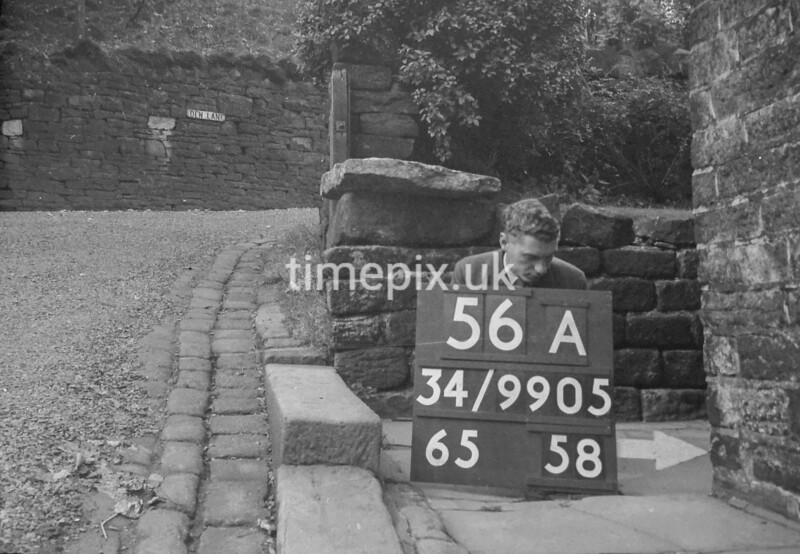 SD990556A, Man marking Ordnance Survey minor control revision point with an arrow in 1950s