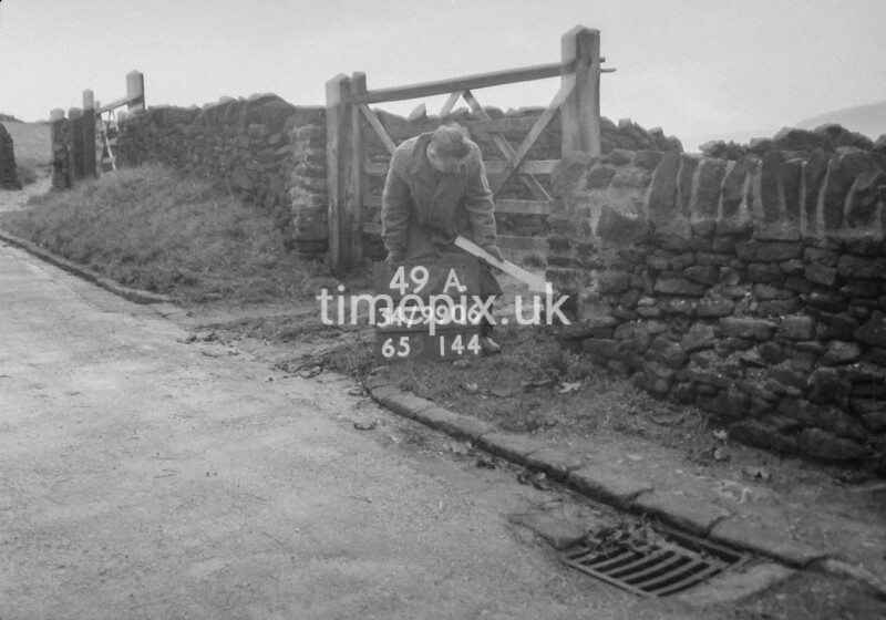 SD990649A, Man marking Ordnance Survey minor control revision point with an arrow in 1950s