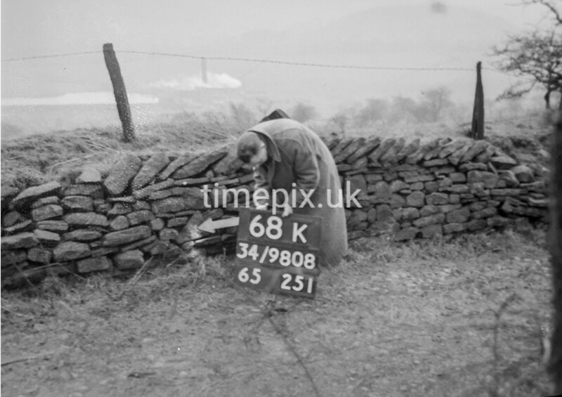 SD980868K, Man marking Ordnance Survey minor control revision point with an arrow in 1950s