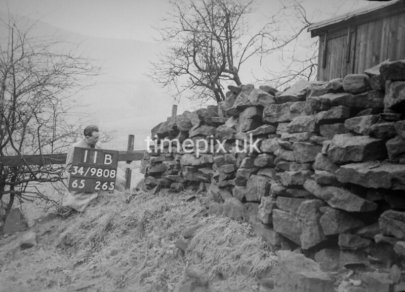 SD980811B, Man marking Ordnance Survey minor control revision point with an arrow in 1950s