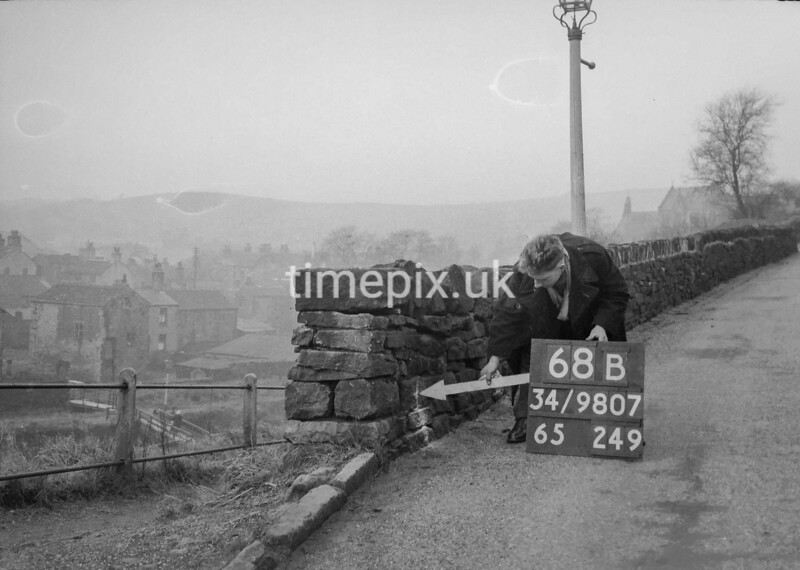 SD980768B, Man marking Ordnance Survey minor control revision point with an arrow in 1950s