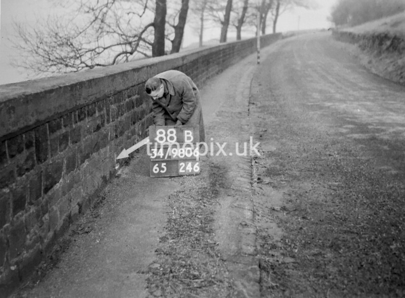 SD980688B, Man marking Ordnance Survey minor control revision point with an arrow in 1950s