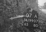 SD990707A, Man marking Ordnance Survey minor control revision point with an arrow in 1950s