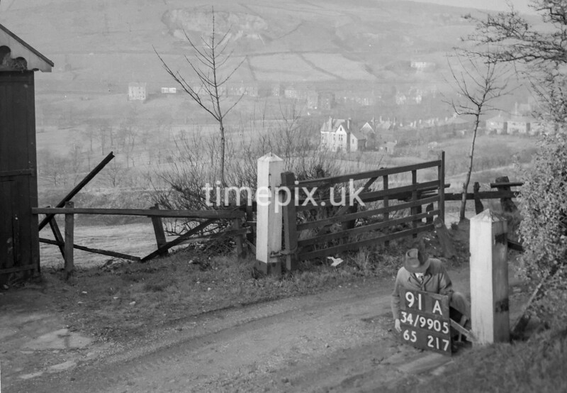 SD990591A, Man marking Ordnance Survey minor control revision point with an arrow in 1950s
