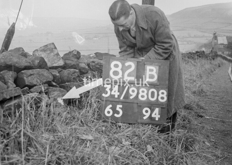 SD980882B, Man marking Ordnance Survey minor control revision point with an arrow in 1950s
