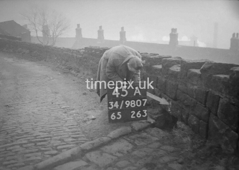SD980745A, Man marking Ordnance Survey minor control revision point with an arrow in 1950s