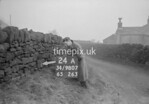 SD980724A, Man marking Ordnance Survey minor control revision point with an arrow in 1950s