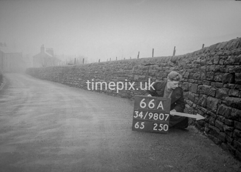 SD980766A, Man marking Ordnance Survey minor control revision point with an arrow in 1950s