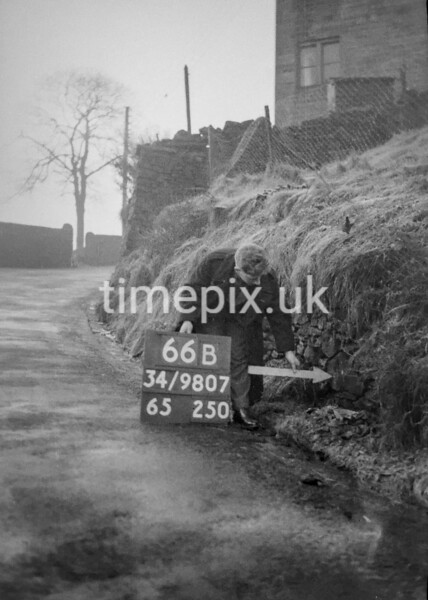 SD980766B, Man marking Ordnance Survey minor control revision point with an arrow in 1950s