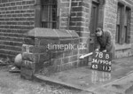 SD990678B2, Man marking Ordnance Survey minor control revision point with an arrow in 1950s