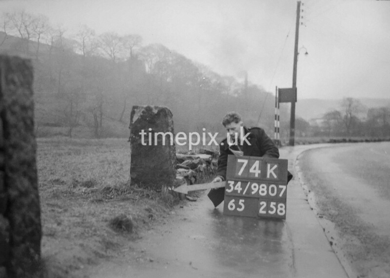 SD980774K, Man marking Ordnance Survey minor control revision point with an arrow in 1950s