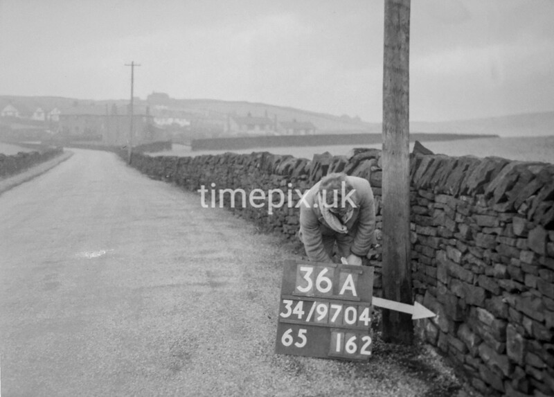 SD970436A, Man marking Ordnance Survey minor control revision point with an arrow in 1950s
