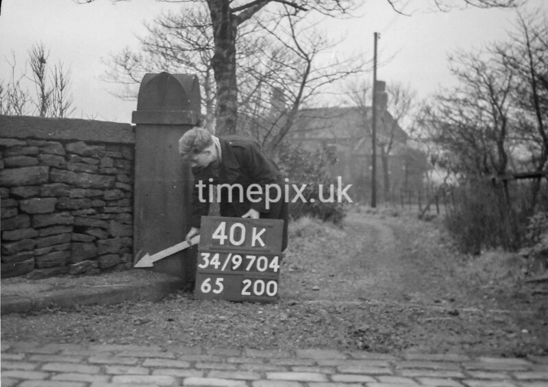 SD970440K, Man marking Ordnance Survey minor control revision point with an arrow in 1950s