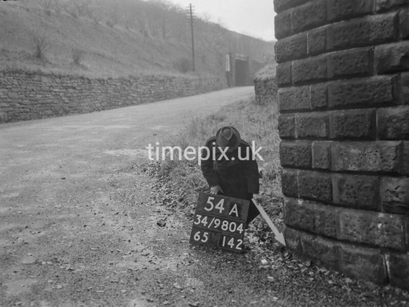 SD980454A, Man marking Ordnance Survey minor control revision point with an arrow in 1950s