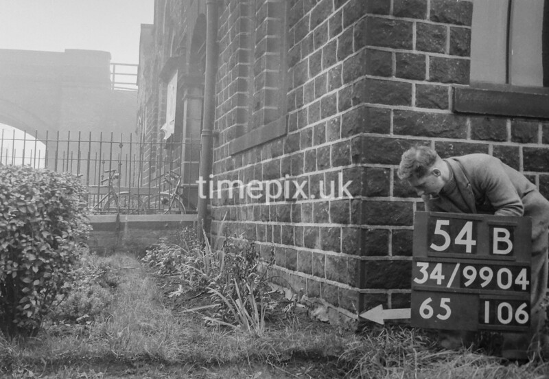 SD990454B, Man marking Ordnance Survey minor control revision point with an arrow in 1950s
