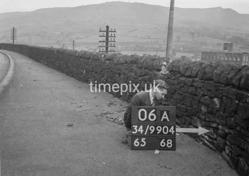SD990406A, Man marking Ordnance Survey minor control revision point with an arrow in 1950s