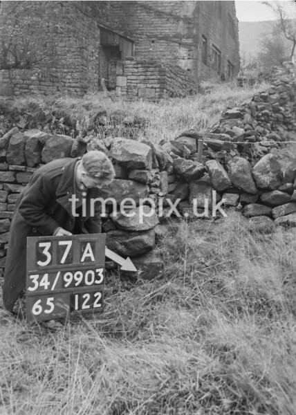 SD990337A, Man marking Ordnance Survey minor control revision point with an arrow in 1950s