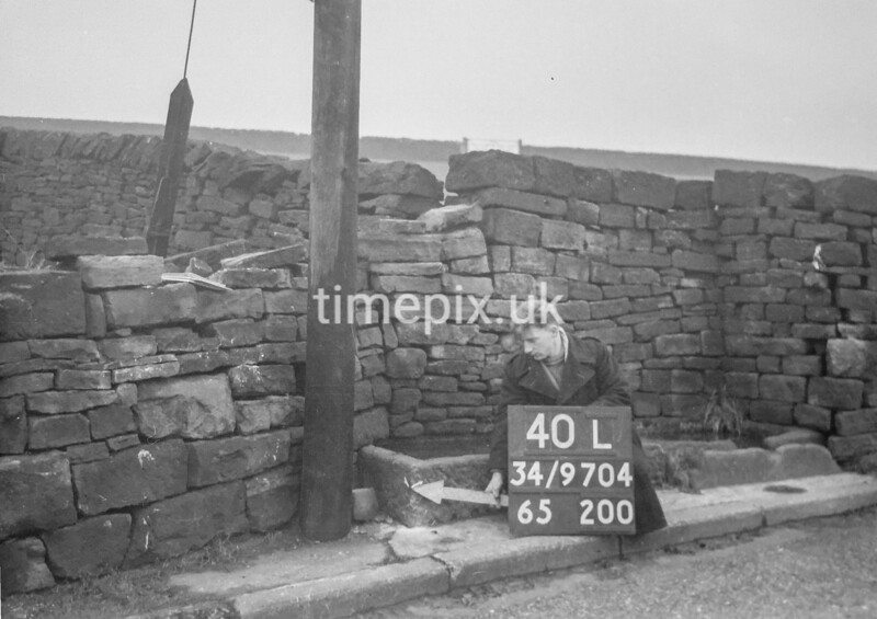 SD970440L, Man marking Ordnance Survey minor control revision point with an arrow in 1950s