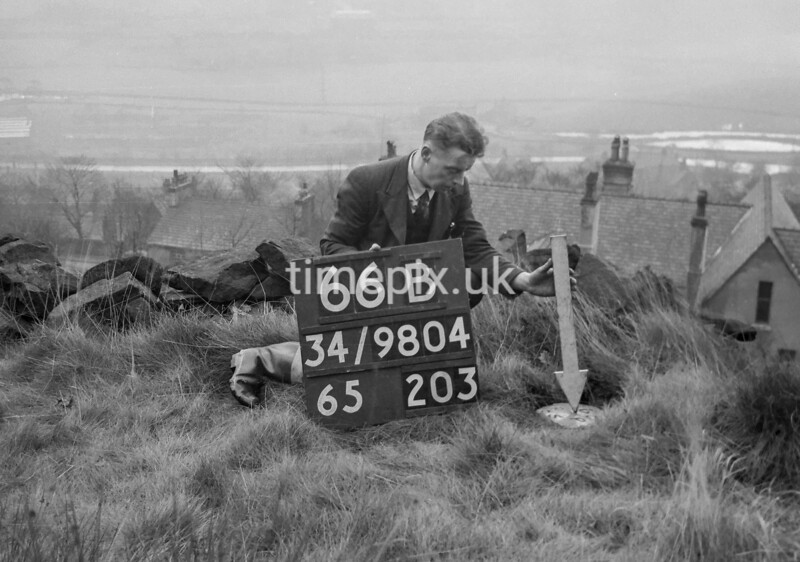 SD980466B, Man marking Ordnance Survey minor control revision point with an arrow in 1950s