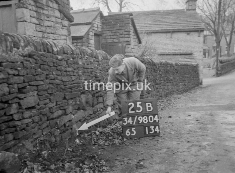 SD980425B, Man marking Ordnance Survey minor control revision point with an arrow in 1950s