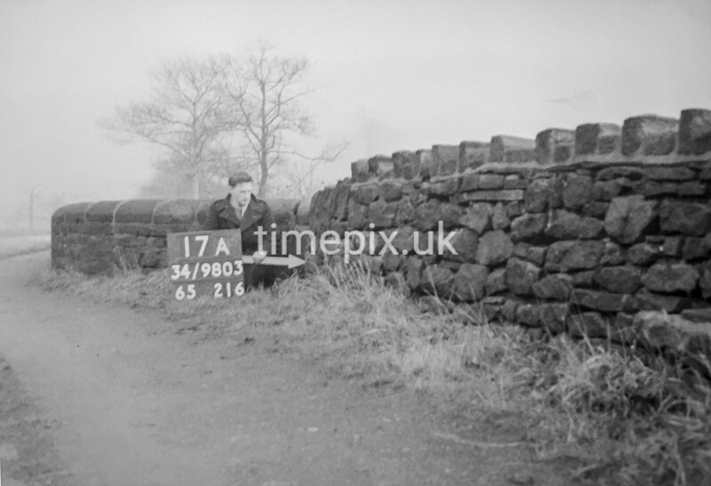SD980317A, Man marking Ordnance Survey minor control revision point with an arrow in 1950s