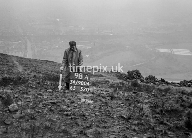 SD980498A, Man marking Ordnance Survey minor control revision point with an arrow in 1950s