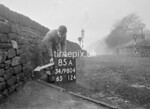 SD980485A, Man marking Ordnance Survey minor control revision point with an arrow in 1950s