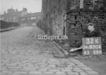 SD970432K, Man marking Ordnance Survey minor control revision point with an arrow in 1950s
