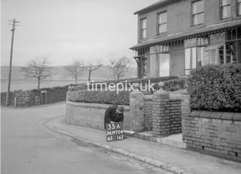 SD970435A, Man marking Ordnance Survey minor control revision point with an arrow in 1950s