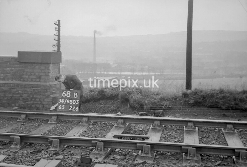 SD980368B, Man marking Ordnance Survey minor control revision point with an arrow in 1950s