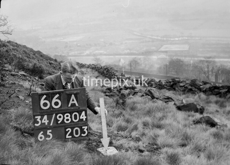 SD980466A, Man marking Ordnance Survey minor control revision point with an arrow in 1950s