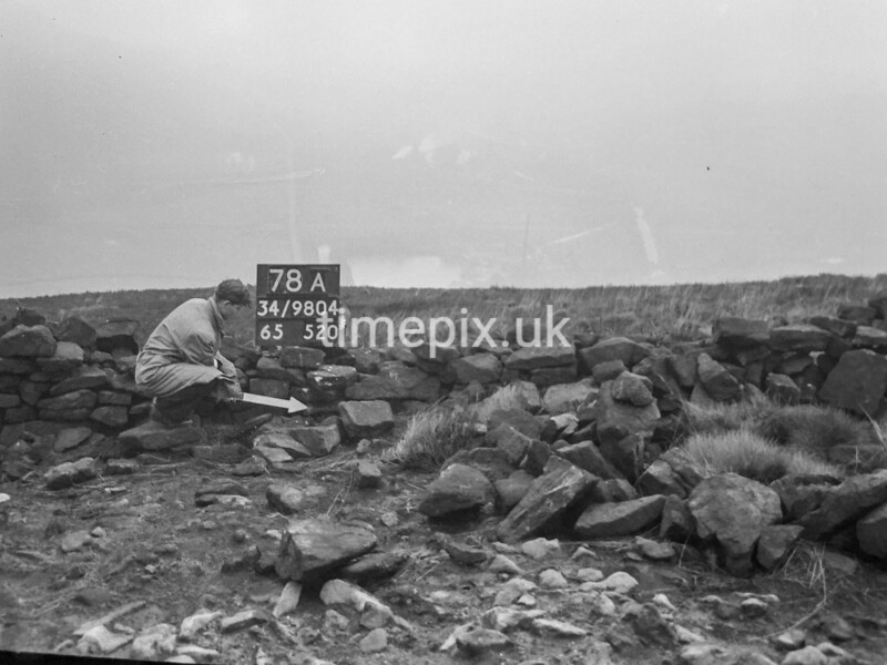 SD980478A, Man marking Ordnance Survey minor control revision point with an arrow in 1950s