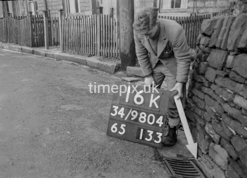 SD980416K, Man marking Ordnance Survey minor control revision point with an arrow in 1950s