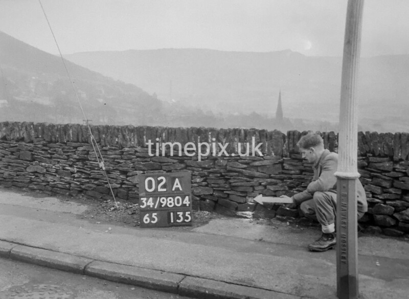 SD980402A, Man marking Ordnance Survey minor control revision point with an arrow in 1950s