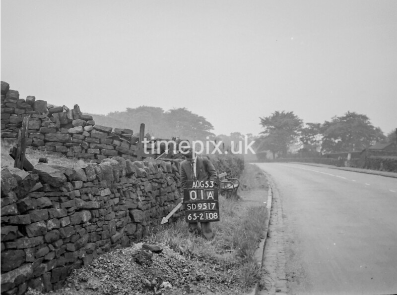 SD951701A, Man marking Ordnance Survey minor control revision point with an arrow in 1950s