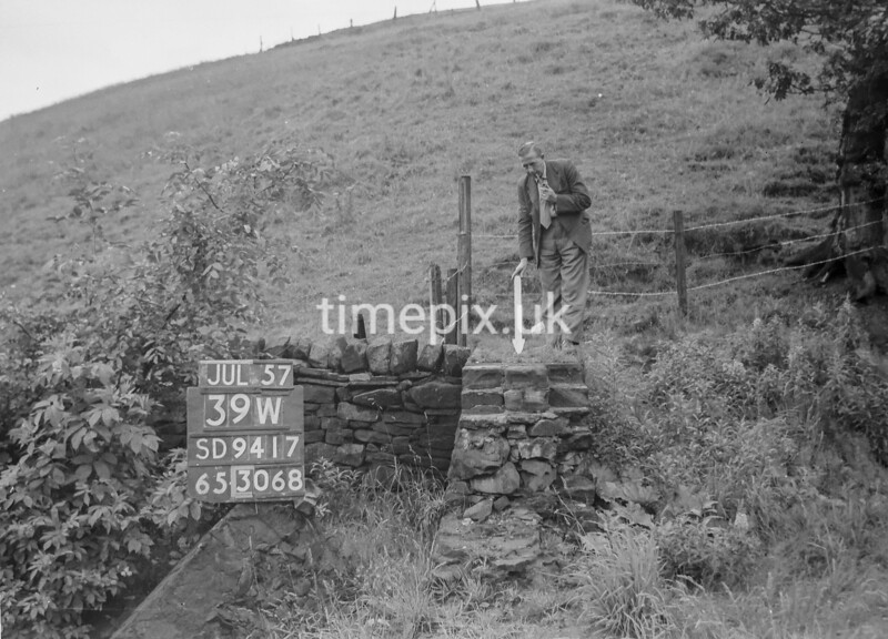 SD941739W, Man marking Ordnance Survey minor control revision point with an arrow in 1950s